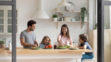 Happy family of four preparing healthy food together at kitchen.
