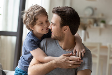 Joyful little preschool boy hugging from back father.