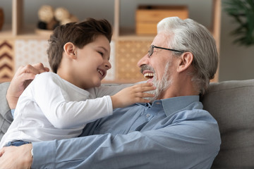 Cute grandson playing laughing bonding with smiling grandfather at home