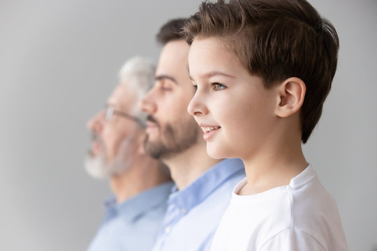 Child boy grandson stand in row with father and grandfather