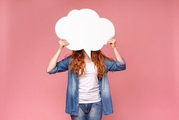 Redhead female hiding her face behind blank white speech bubble