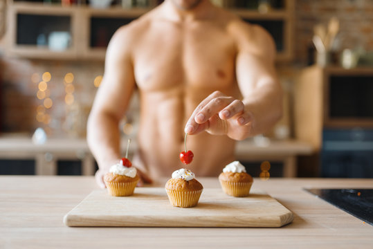 Man with naked body cooking cakes with cherry