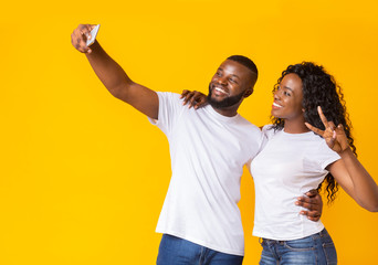 Black couple in love making selfie over yellow studio background