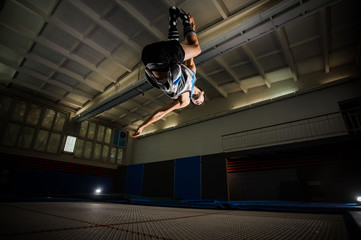 Man making tricks on the trampoline in the gym