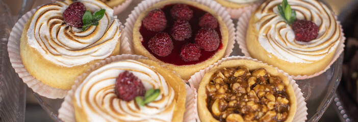 mini tart with fresh fresh raspberries and blueberries, peanuts and caramelon a large glass tray, food closeup. Long banner format. Header for web site.