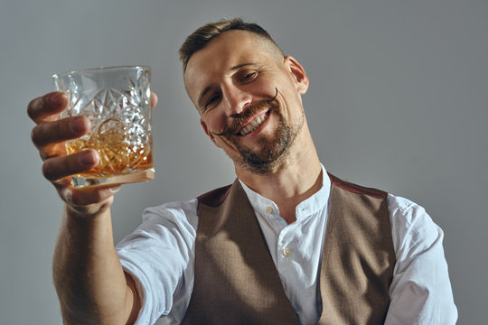 Man with stylish mustache, dressed in classic brown vest, white shirt is sitting at the table, enjoying whiskey. Grey background, close-up shot.