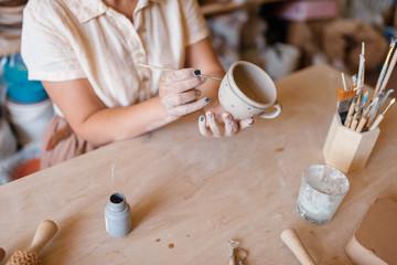 Female master paints a pot, pottery workshop
