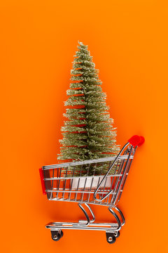 Shopping cart with christmas tree on red table.