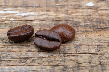 Grains of coffee on an old wooden surface.