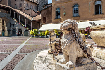 Fototapete - Bergamo in summer, Italy. Piazza Vecchia in Citta Alta or Upper City. Lion statues with chains at the vintage fountain in the ancient Bergamo center. Antique architecture of Old town of Bergamo.