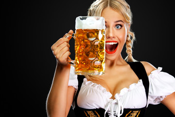 Smiling young sexy oktoberfest girl waitress, wearing a traditional Bavarian or german dirndl,...