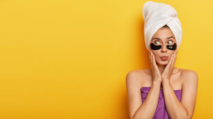 Horizontal shot of pretty female model keeps lips rounded, applies black hydrogel patches under eyes, has sensual skin, wears wrapped towel on head, isolated over yellow studio wall with empty space Wall mural