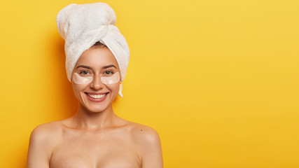 Studio shot of beautiful young woman with healthy delicate fresh skin under eyes, wears towel on head, applies patches for reducing fine lines, stands naked against yellow background. Spa treatment Wall mural