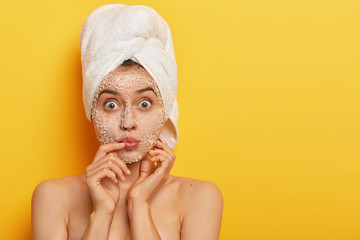 Impressed young woman keeps lips rounded, has wide opened eyes, applies sea salt scrub, wears wrapped towel on head, has delicate soft skin, models indoor. People, spa, peeling, freshness concept Wall mural