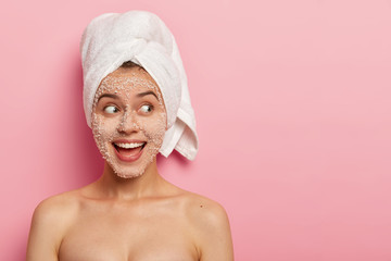 Portrait of happy female model applies sea salt scrub on face, has positive expression, looks aside, has naked body, wears towel after bath, poses over pink wall with copy space, uses beauty product