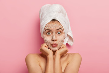 Horizontal shot of surprised Caucasian woman keeps palms under chin, looks with widely eyes, applies scrub mask, avoids problems with skin, stands shirtless against pink background. Beauty concept