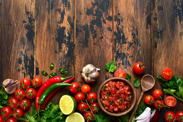 Tomato salsa (salsa roja) - traditional mexican sauce  with ingredients for making. Top view with copy space. Wall mural