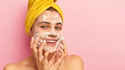 Cropped image of happy Caucasian woman smiles happily, keeps hands on both cheeks, washes face with hygienic product, has soap on skin, enjoys softness and freshness, isolated on pink studio wall