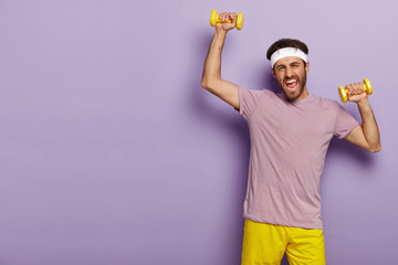 Horizontal shot of motivated sportsman trains muscles, raises yellow dumbells, wears headband, casual outfit, being active, poses over purple studio wall, wants to have strong biceps. Sporty lifestyle