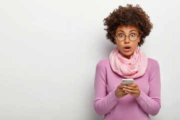 Photo of surprised curly haired woman wears glasses, holds mobile phone, gets message, looks with shocked expression at camera, wears round eyewear, casual outfit, poses indoor. People, lifestyle