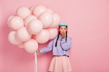 Beautiful dark haired lady with specific appearance, wears makeup, keeps lips rounded, blows air kiss at camera, has flirty expression, poses with helium balloons, isolated over pink background