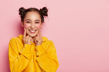 Photo of beautiful brunette woman with two buns, points index fingers on cheeks, dressed in casual corduoy yellow sweatshirt, wears bright pinup makeup, stands against rosy wall, free space.