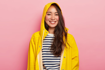 Smiling beautiful woman enjoys wearing warm striped jumper, yellow raincoat with hood, has good mood, goes out with friends during rainy day, poses indoor. People, weather and season concept