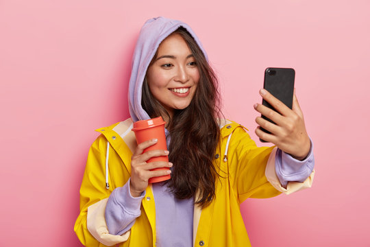 Teenage girl with specific appearance takes selfie portrait, has outdoor walk during autumn day, wears protective raincoat, drinks coffee from flask, smiles at camera, stands indoor, enjoys stroll