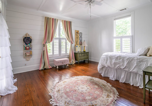 Bedroom in Old House with wood floors Pink and White Bedspread and Original shiplap