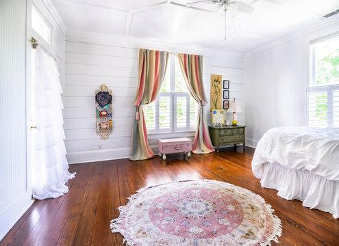Bedroom with shiplap walls, rug, ruffles, pastels, wood floors