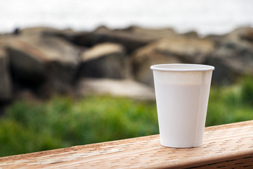 A disposable paper cup of coffee placer on a wooden table over a nature background, outdoors, close up.