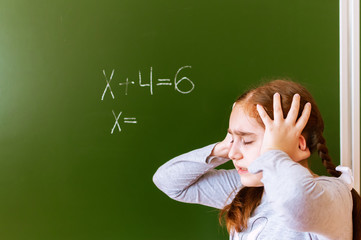 Schoolgirl solves a math problem on the blackboard during the lesson.