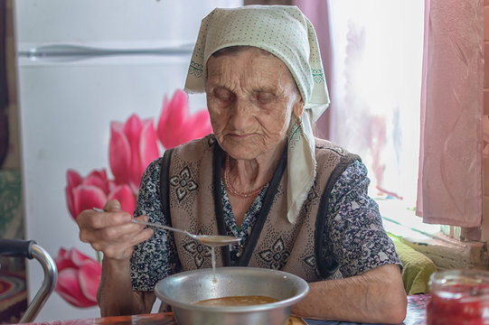 The old woman eats soup, charity food for the poor pensioners, social reform