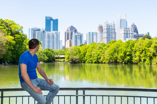 Young man sitting on railing in Piedmont Park in Atlanta, Georgia looking at cityscape skyline urban view with city skyscrapers downtown by Lake Clara Meer