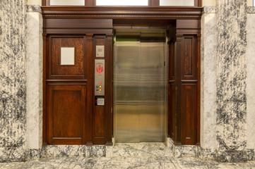 Old elevator with metal doors and wood grain paneling