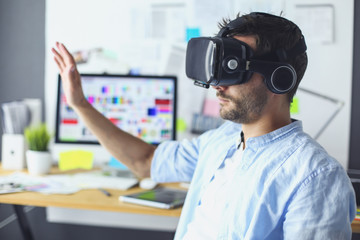 Young male software programmer testing a new app with 3d virtual reality glasses in office.