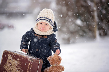 Baby playing with teddy in the snow, winter time. Little toddler boy in blue coat, holding suitcase and teddy bear, playing outdoors in winter park
