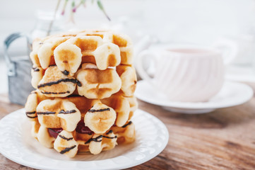 Fresh round Belgian waffles with a layer of jam poured with chocolate on a white plate with a Cup of tea. Close up