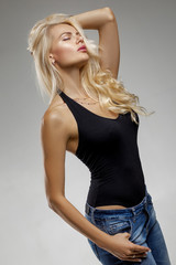 beautiful sensual blonde woman in a black T-shirt and jeans posing in studio