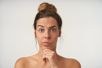 Indoor shot of puzzled pretty woman wearing bun hairstyle and no make-up, holding chin with hand and looking to camera with raised eyebrow