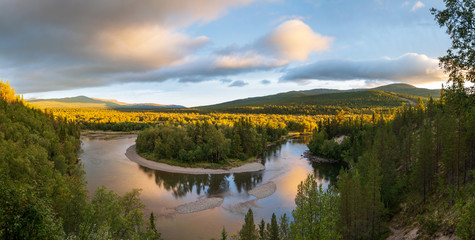 Fotomurales - A shallow river in the green hills of Jamtland, Sweden, during sunrise.
