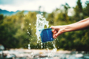 Blue camping mug with clear water, splashes on a forest background. Clear water from a mountain river, ecology concept
