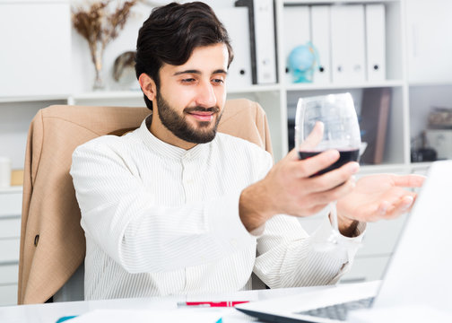 Manager with glass of wine having online conversation