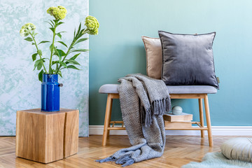 Stylish scandinavian interior of living room with wooden bench, colorful pillows, plaid, wooden cube, flowers in vase, books and elegant personal accessories. Interior design and modern home decor.