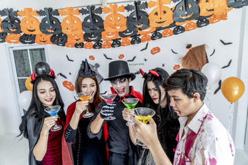 Group of young friends dressed in Halloween costumes are posing at club party Wall mural