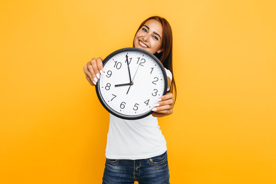 Young attractive woman with a watch on a yellow background