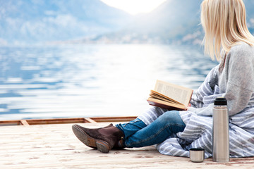 Woman is reading book on wooden pier by winter sea, mountains, beach. Cozy picnic with coffee, hot...