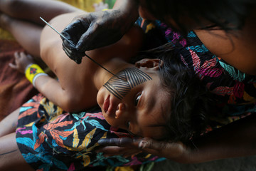 Kayapo indigenous woman paints her daughter with a Kayapo traditional drawing in Bau village near Novo Progresso