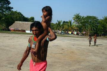 Kayapo indigenous man carries a child in Bau village near Novo Progresso