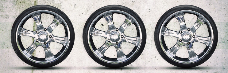 Car wheel on gray concrete background. Copy space. Transport. Spare parts.
